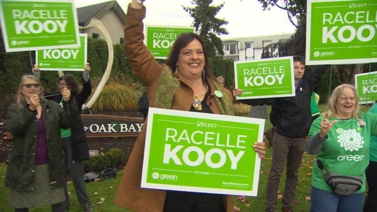 Plusieurs personnes tiennent des pancartes dans les airs, sur lesquelles il est écrit en anglais : Élisez Racelle Kooy. Une affiche derrière elles indique Oak Bay.