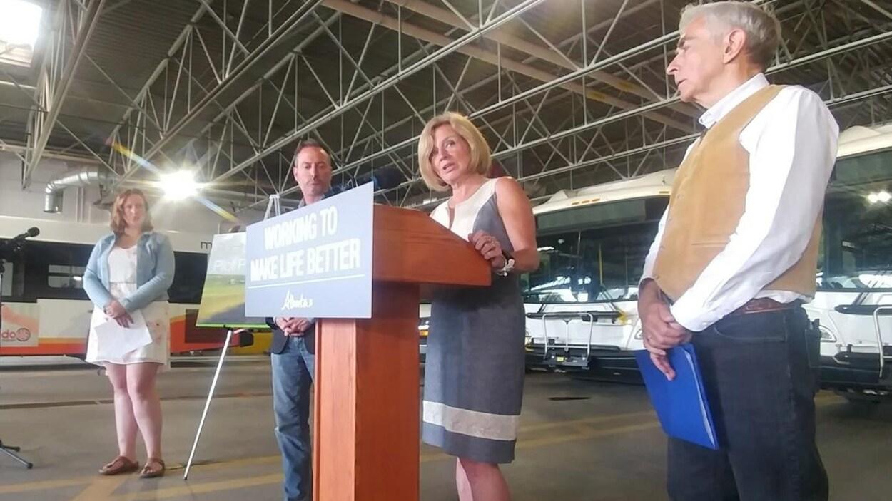 Une femme parle depuis un podium, entourée de trois autres personnes qui la regardent.