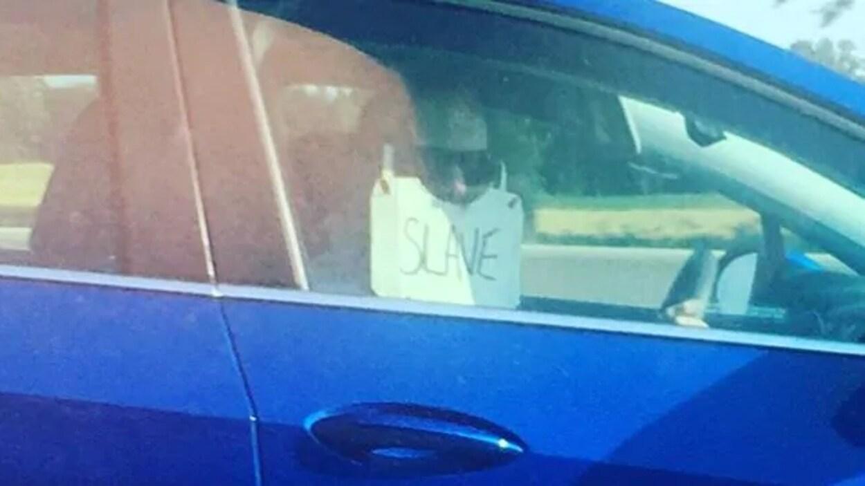 Un automobiliste porte une sorte de masque sur lequel on peut lire « esclave ».
