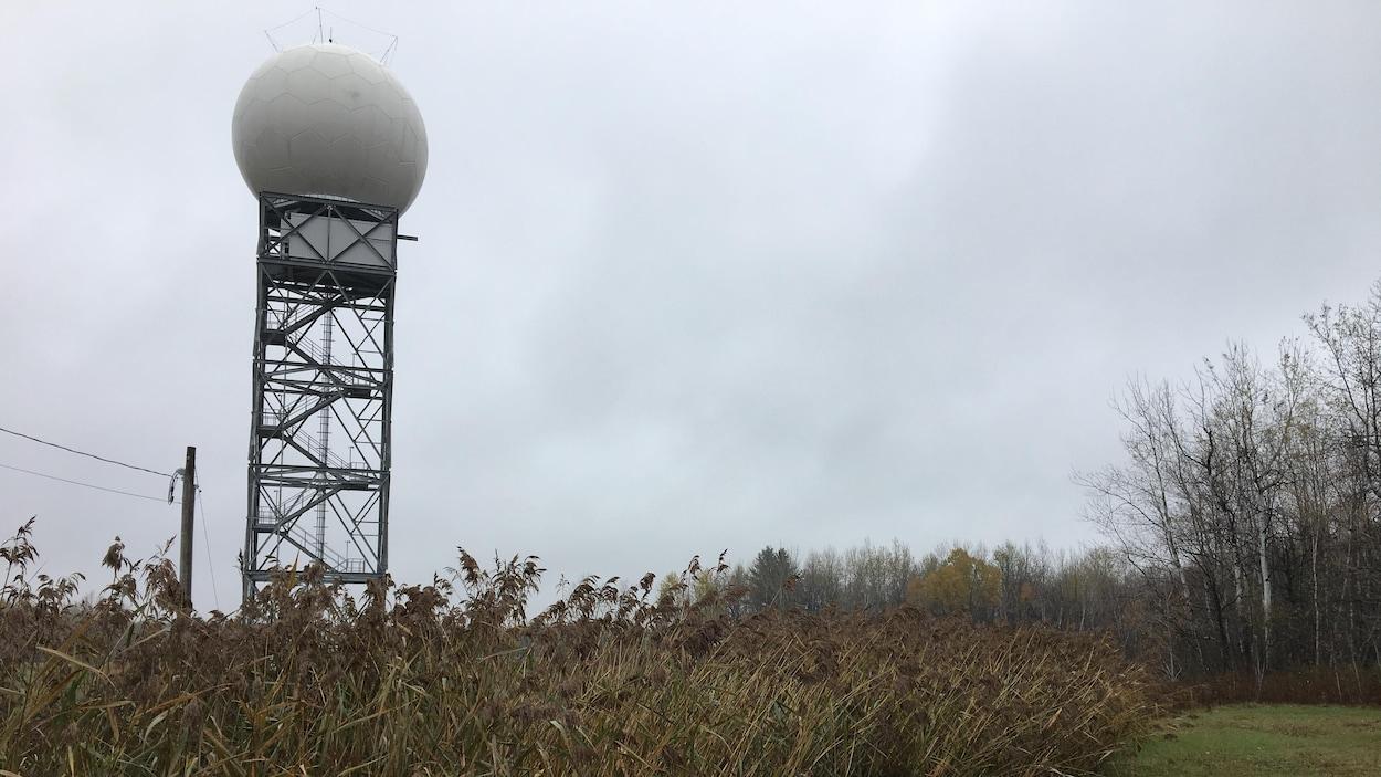 Un radôme, semblable à une grosse balle de golf, est juché sur une structure de métal dans un champ à l'automne.