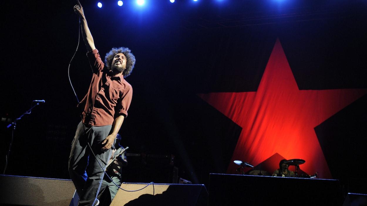 Le chanteur Zach de la Rocha lève le bras pendant un concert de Rage Against the Machine.