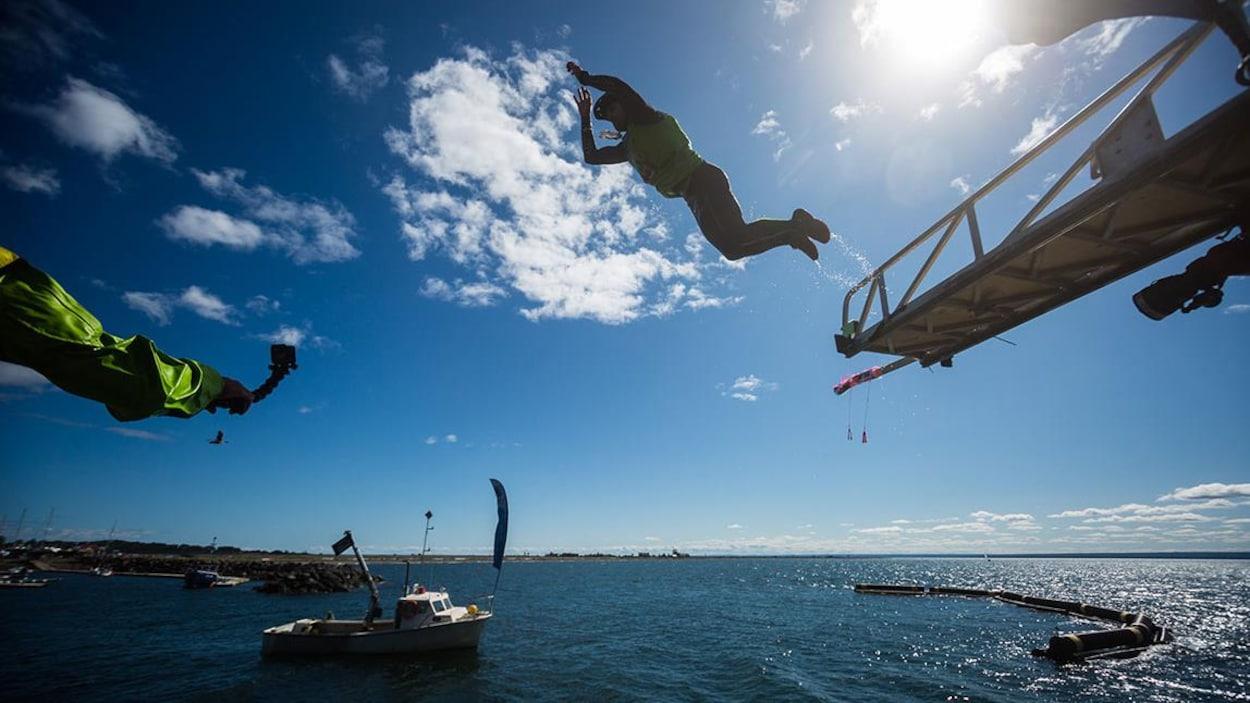 Participants au dessus de l'eau qui sautent d'une plateforme à une autre.