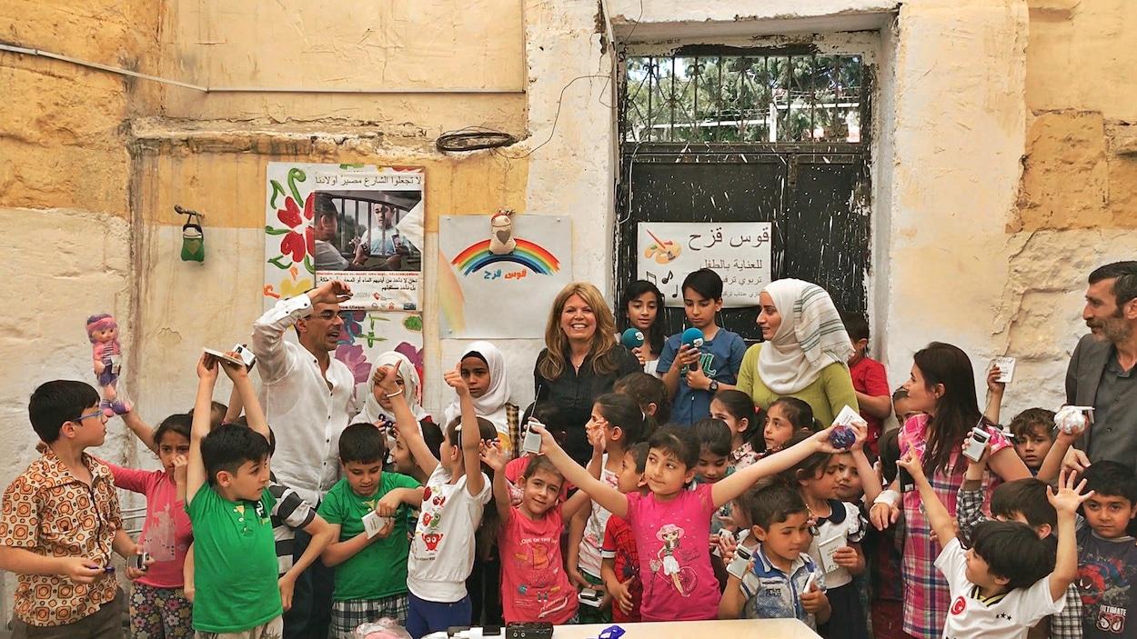 Les enfants réfugiés syriens lèvent les bras de joie après avoir reçu leurs radios.