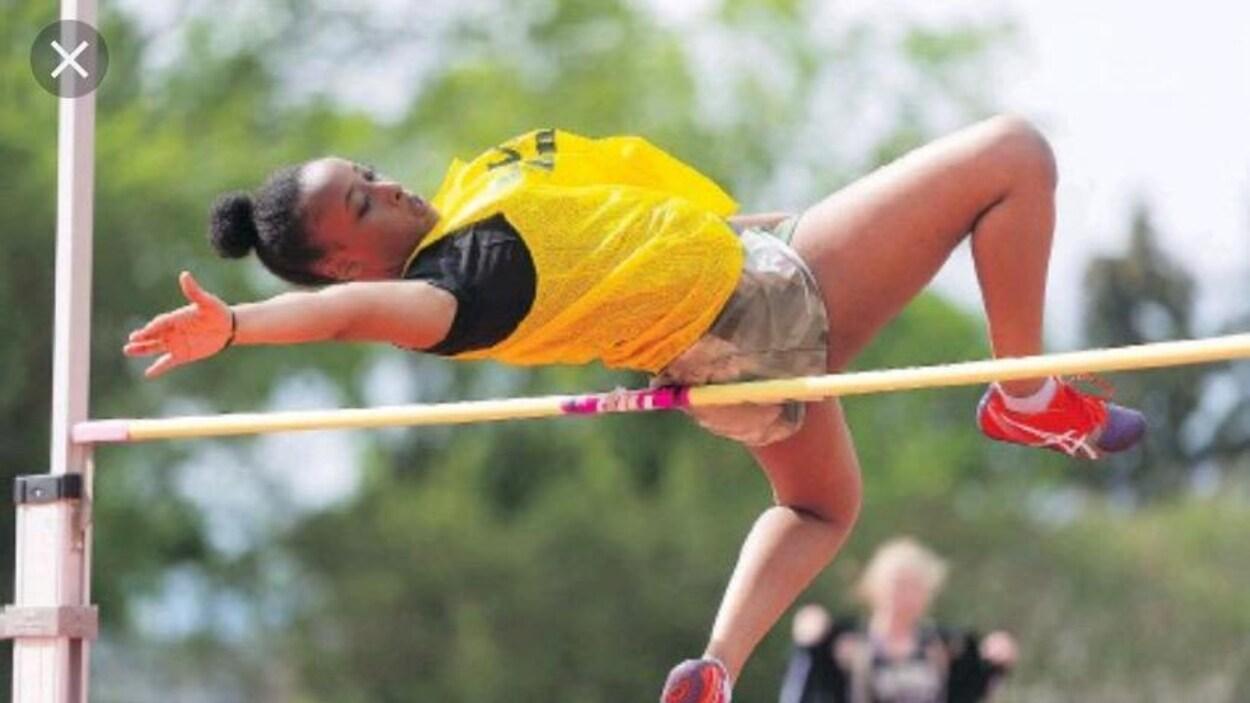 Une jeune femme photograpiée pendant qu'elle franchit une barre dans une épreuves de saut en hauteur.