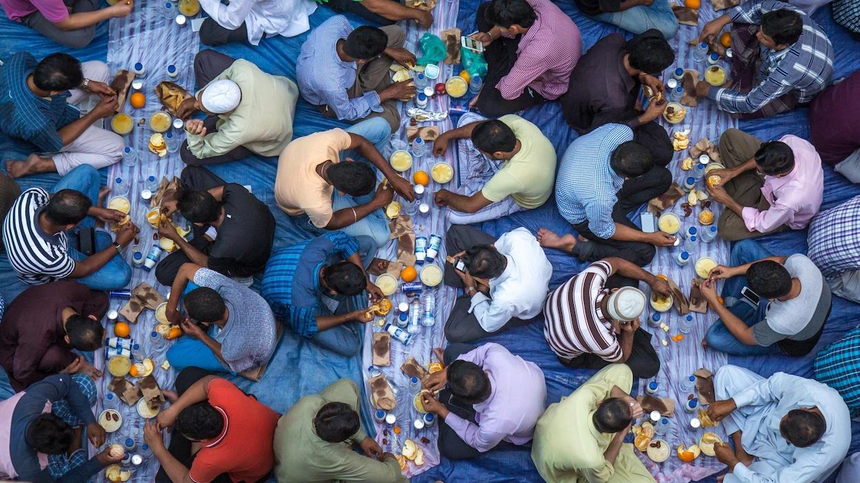 Des hommes mangent, assis sur des nappes déposées par terre, dans une mosquée lors du ramadan.