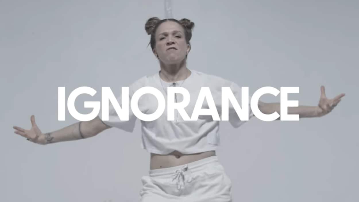 Une femme danse. Le mot « ignorance » apparaît devant elle.