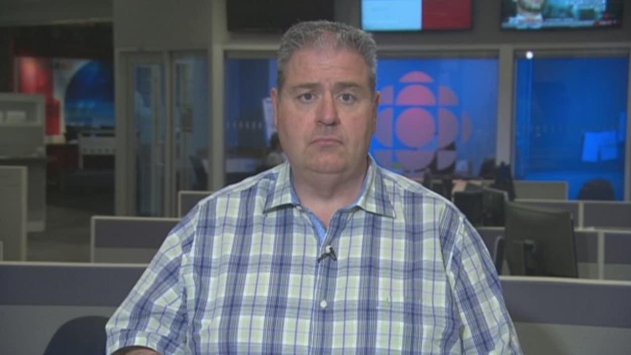 Un homme en chemise à carreaux devant les écrans d'ordinateur d'une salle de nouvelles aux couleurs de Radio-Canada.