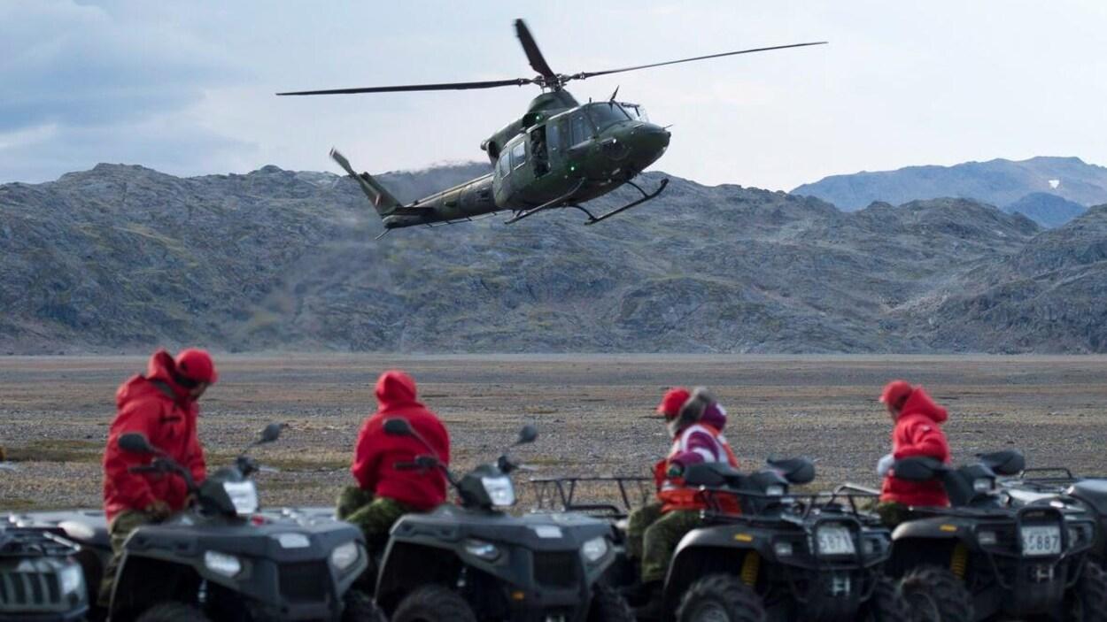 Des Rangers assis sur des VTT regardent un hélicoptère se poser.