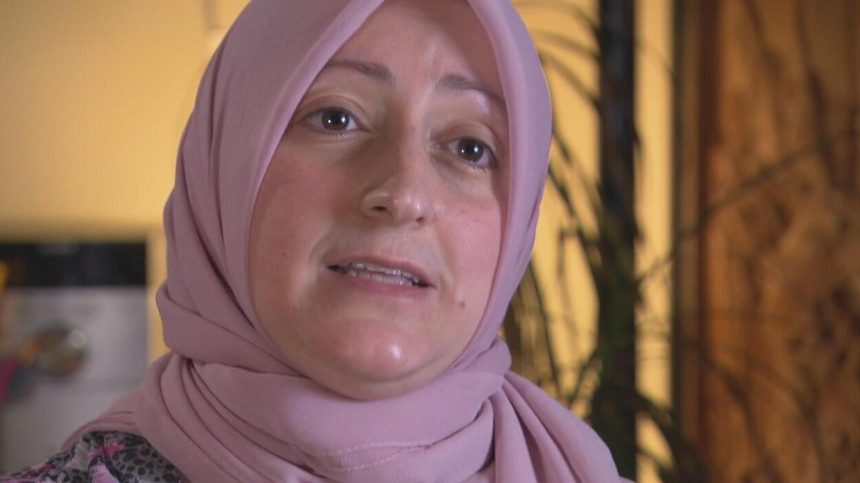 Une femme portant un hijab rose pâle