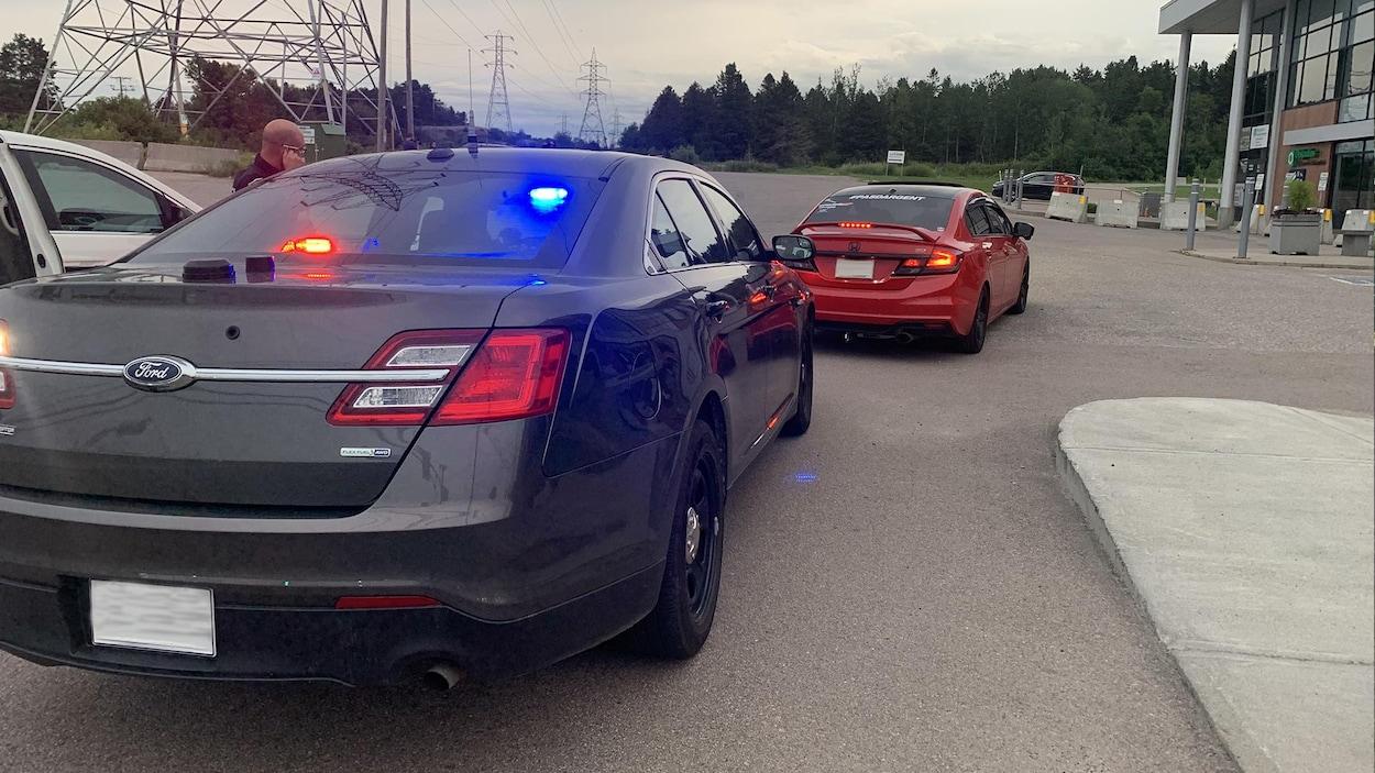 Un automobiliste arrêté dans le stationnement d'un commerce.