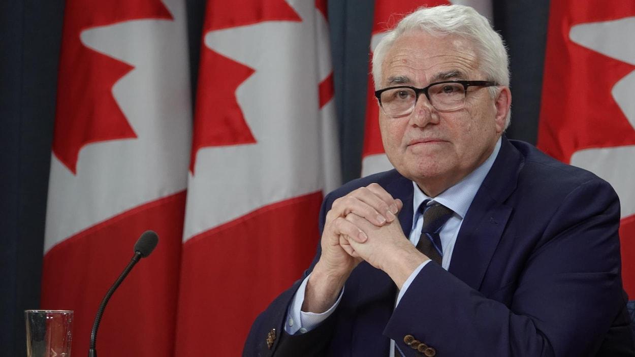 M. Théberge s'adresse aux médias, assis à une table, devant des drapeaux canadiens.