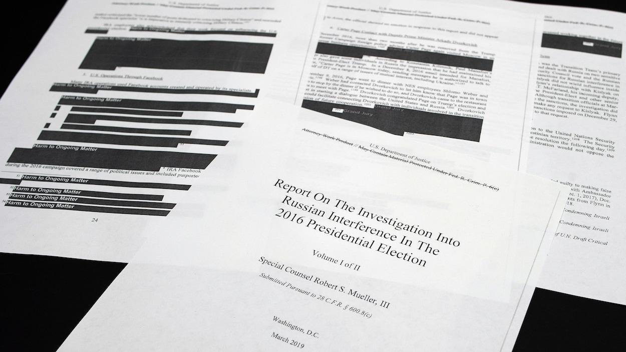 Quatre pages du rapport Mueller, dont la page titre, sont étalées sur une table. On peut voir des sections caviardées.