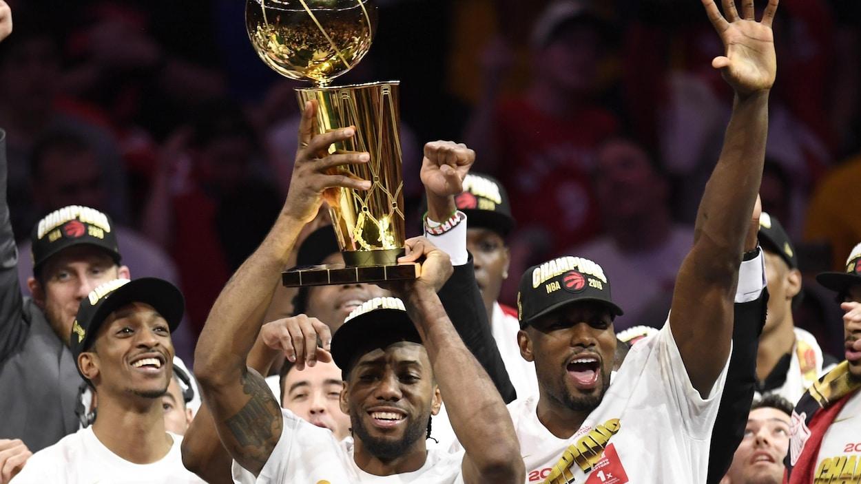 Photo d'un homme qui tient dans les airs un trophée avec un ballon de couleur or.
