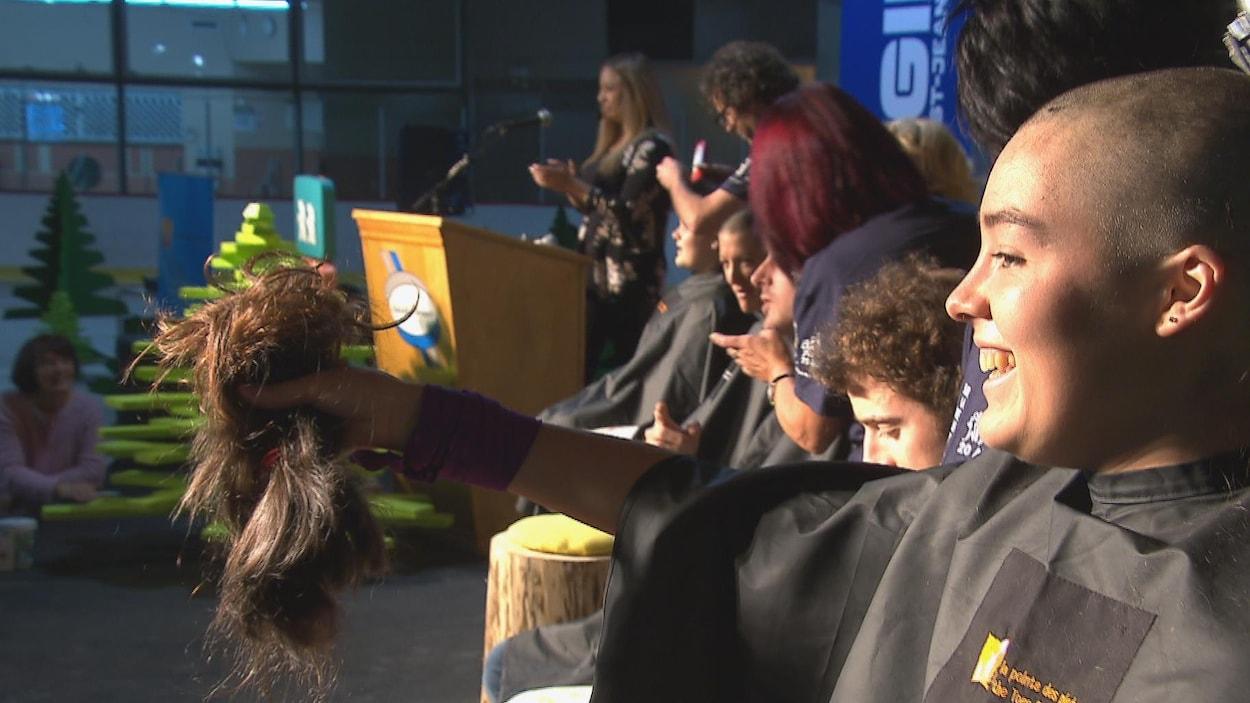 Une participante du Rase-O-Thon Marie-Hélène Côté montre les cheveux qu'elle a fait couper.