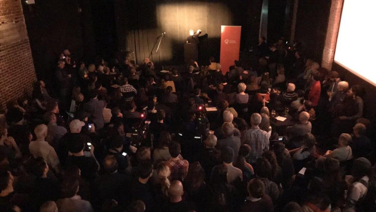 Des gens écoutent des discours dans une salle remplie à pleine capacité.