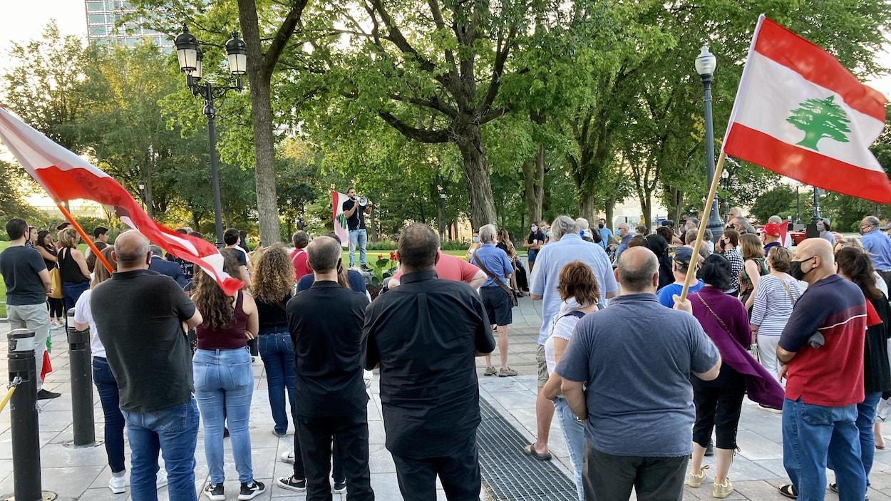 Un peu plus de cinquante personnes, de dos, regardent un homme avec un mégaphone parler. Plusieurs drapeaux du Liban sont visibles dans la foule.
