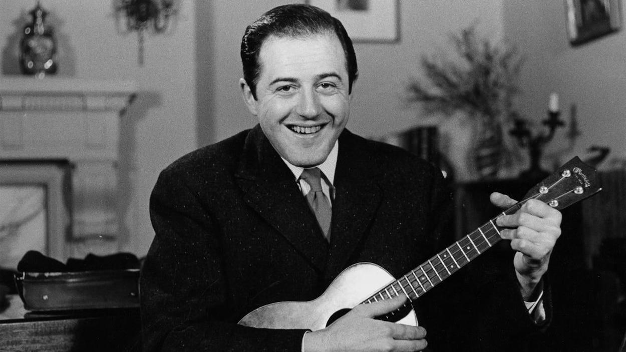 Le chanteur Raymond Lévesque, une guitare à la main, dans le salon de sa résidence.