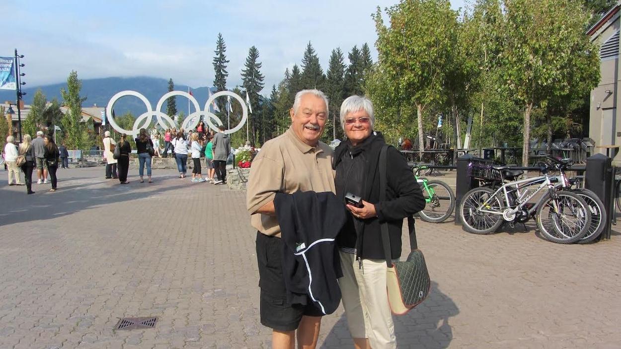Raymon Bisson et Lorraine Bisson sourient devant les anneaux olympiques.