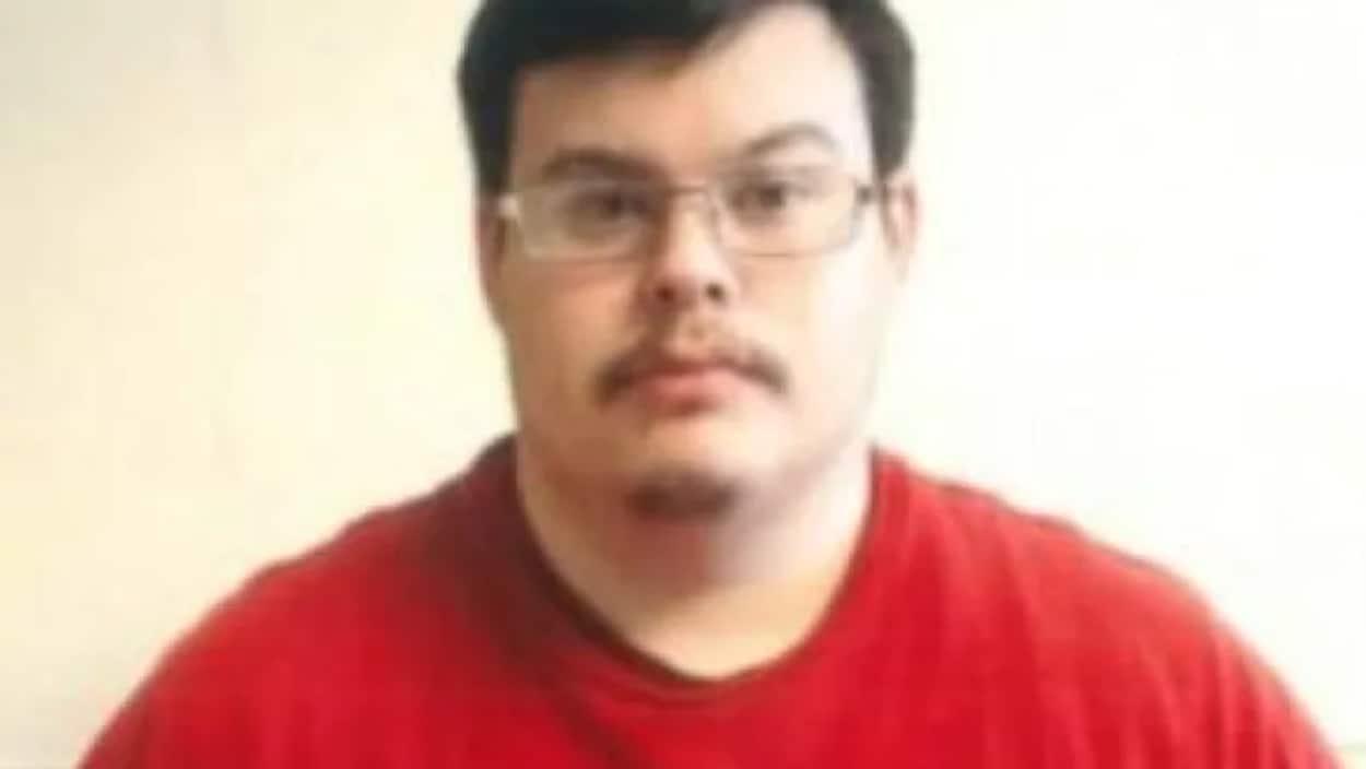 Un homme avec des lunettes et un chandail rouge.