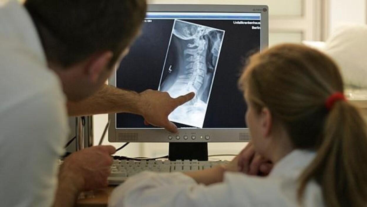 Un homme et une femme examinent une radiographie des vertèbres du cou d'une personne sur un écran d'ordinateur.