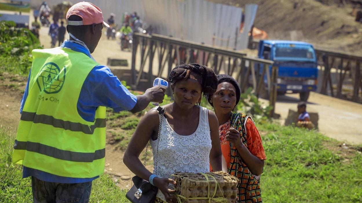 Un employé de l'OMS prend la température des personnes à la frontière entre le Congo et l'Ouganda.