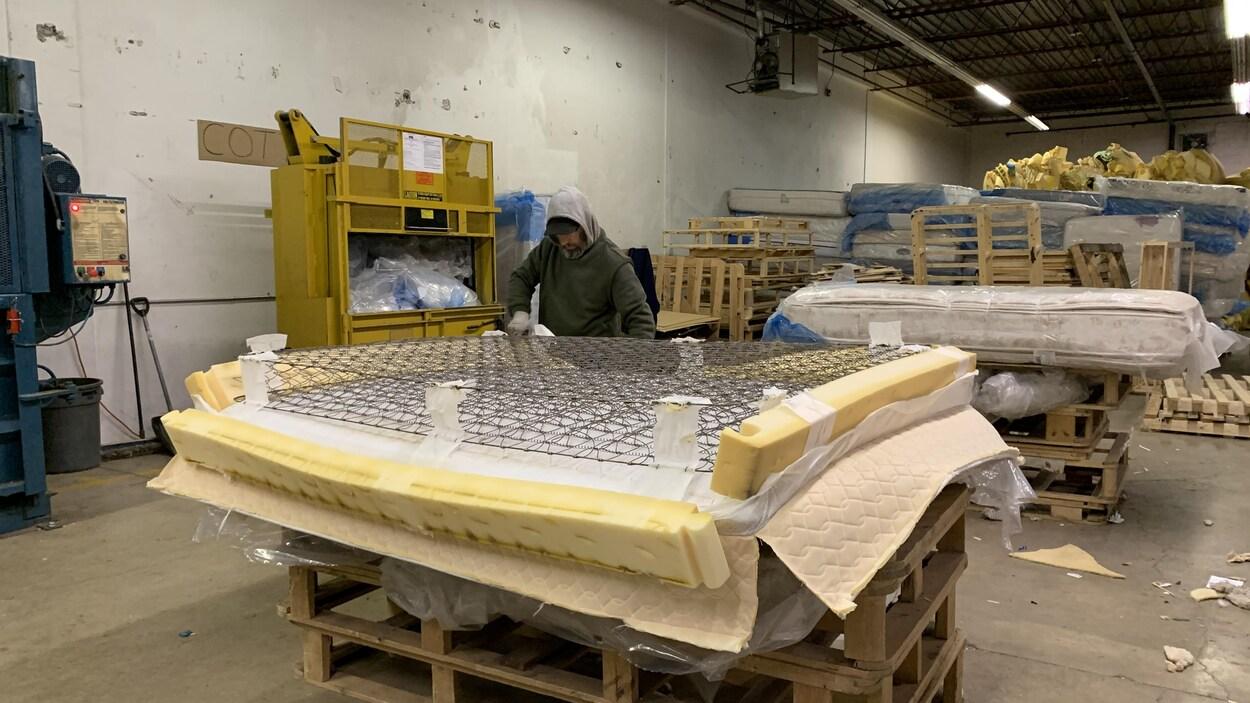 Un travailleur vêtu de gants enlève le métal d'un matelas découpé, dans un petit entrepôt.