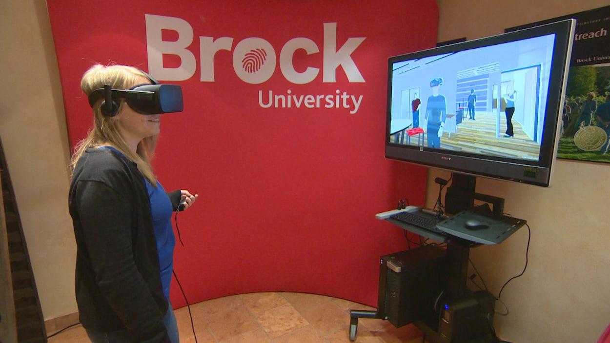 Une femme se tient debout avec des lunettes de réalité virtuelle, devant un écran de télévision ou on voit une pièce virtuelle.