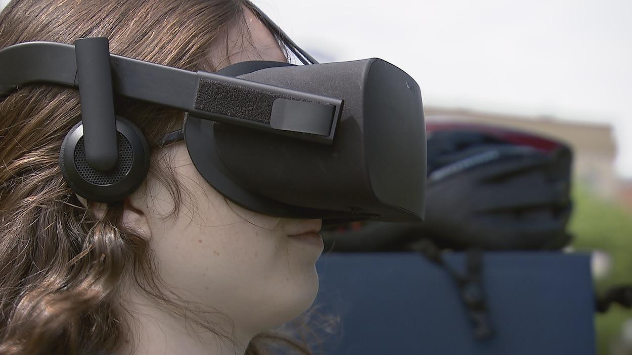 Une jeune conductrice participe à la simulation après avoir enfilé un casque de réalité virtuelle.