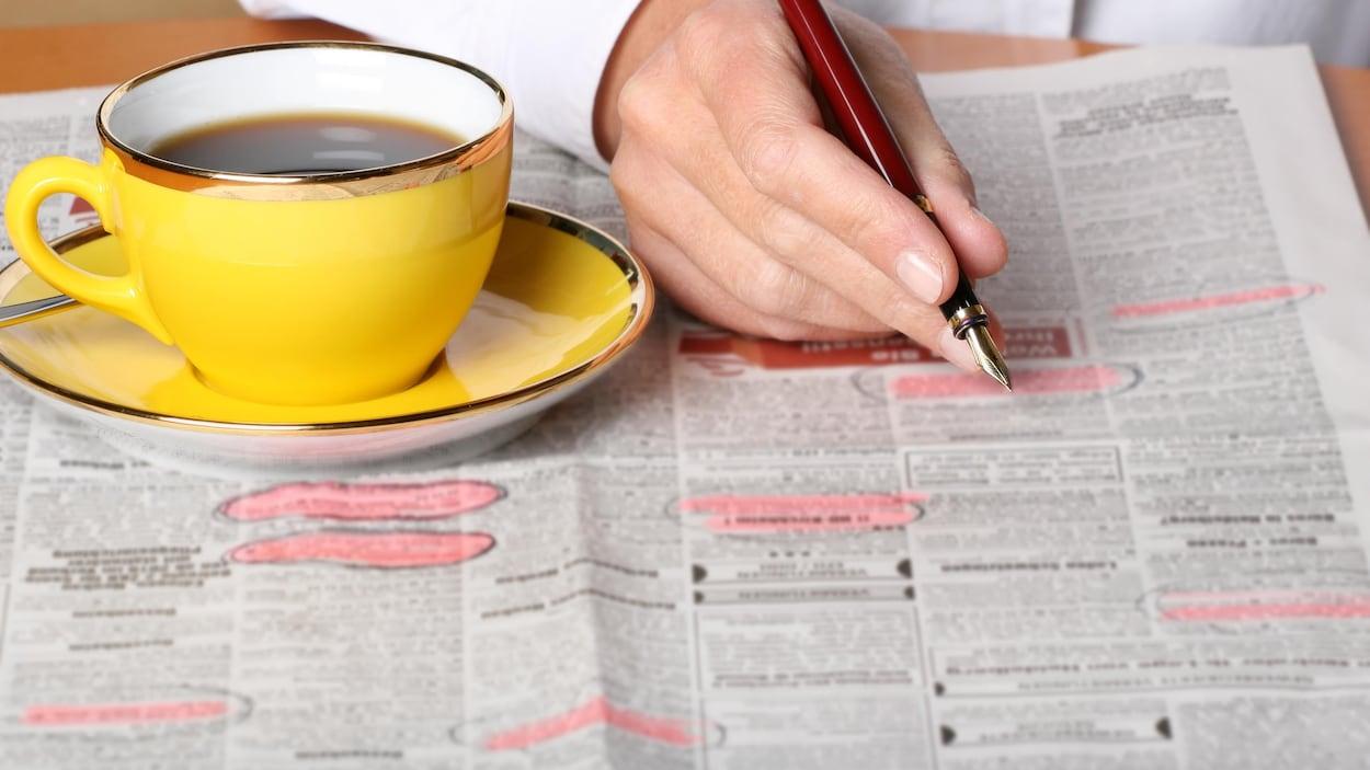 Une personne consulte les petites annonces d'un journal, à la recherche d'un emploi.