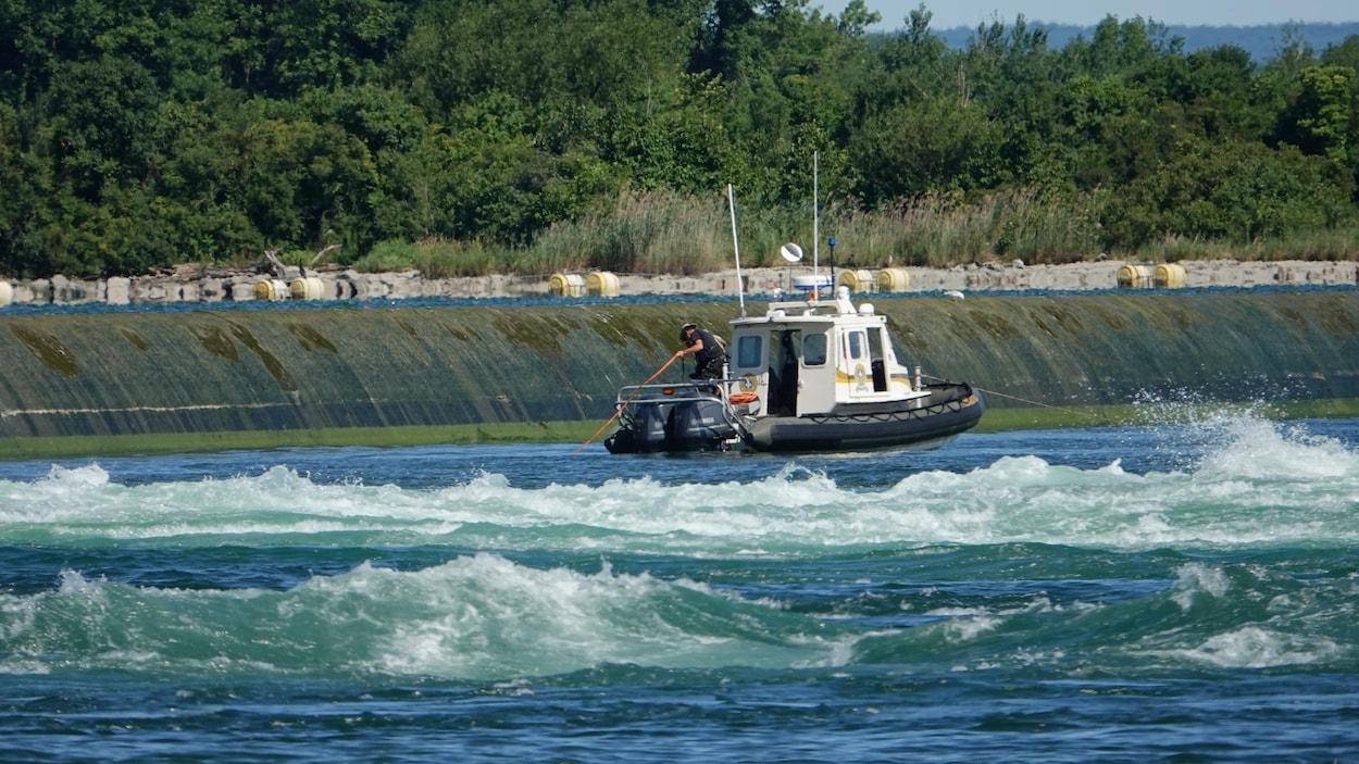 Un policier manie une gaffe depuis un bateau.