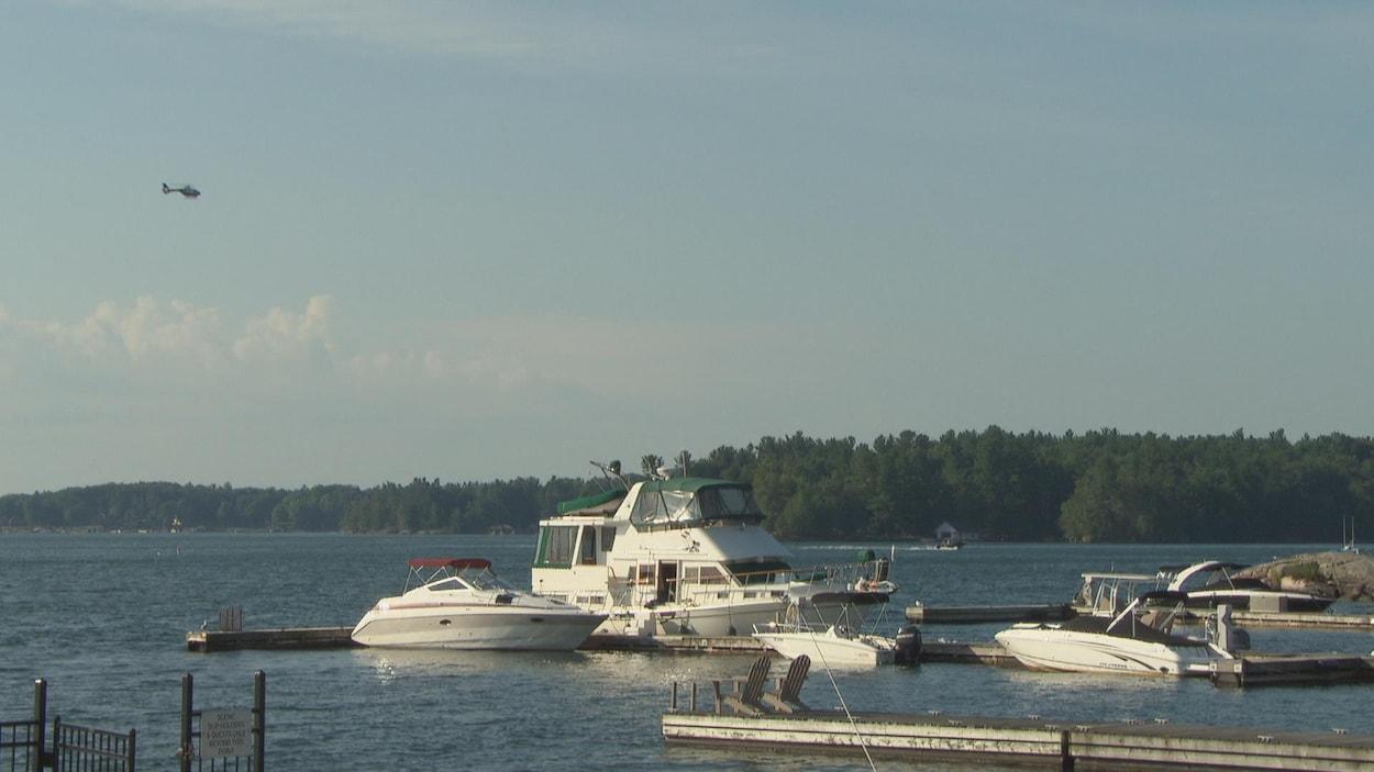 Un hélicoptère survole un lac où des bateaux sont amarrés au quai