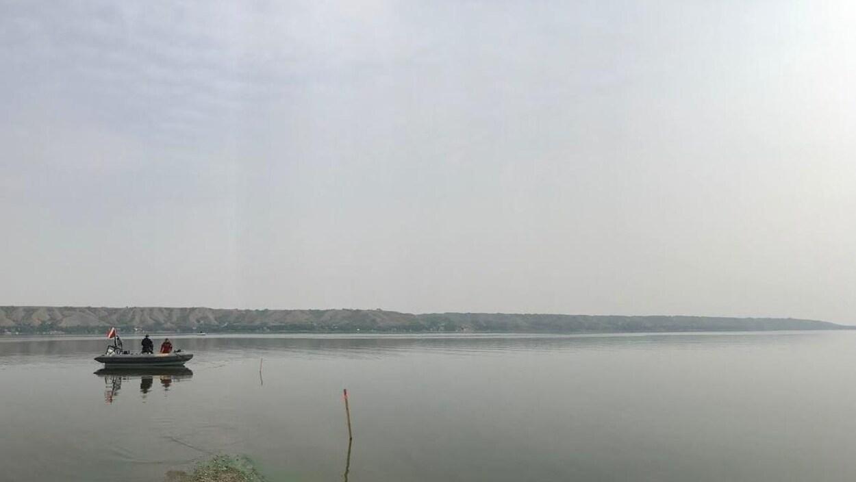 Un petit bateau sur un lac aux eaux calmes, contenant deux personnes.