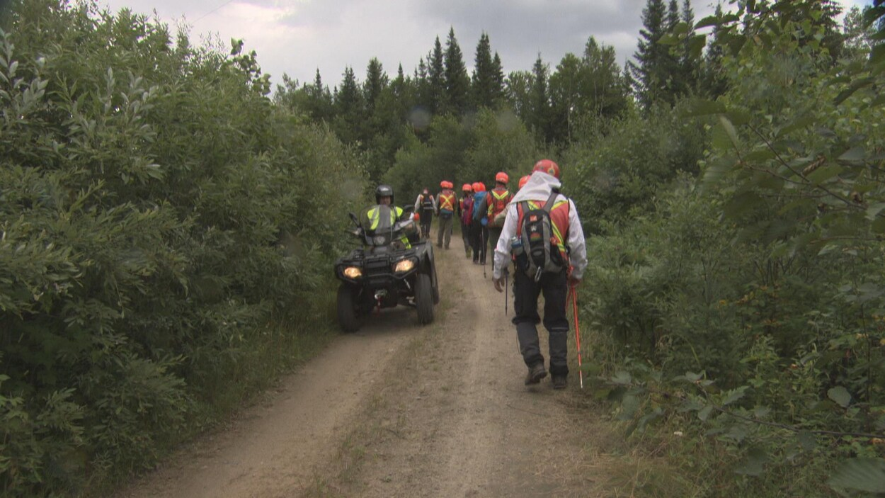 Des marcheurs et un agent en véhicule tout-terrain dans un sentier boisé lundi.