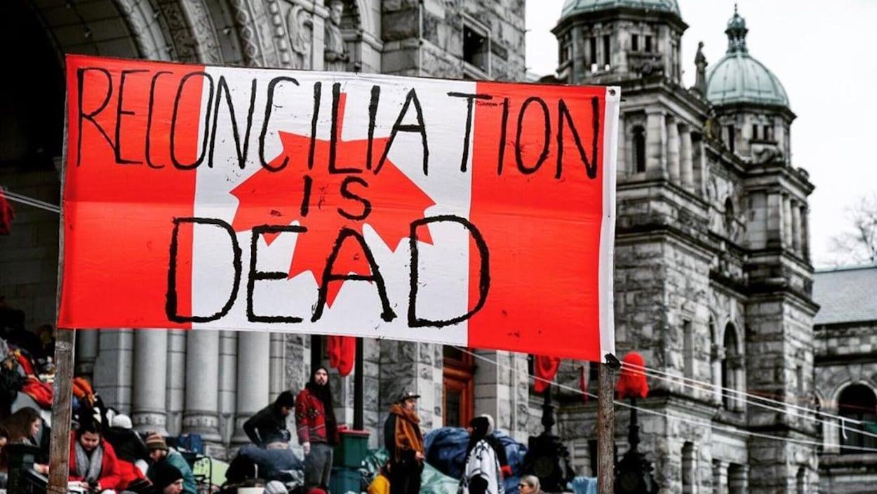 Un drapeau canadien à l'envers, où il est inscrit que la réconciliation est morte.