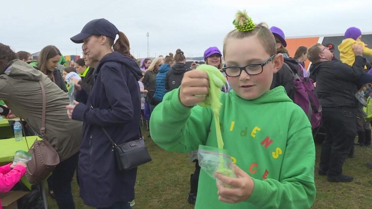 Un enfant manipule de la glu verte et porte un chandail vert assorti.