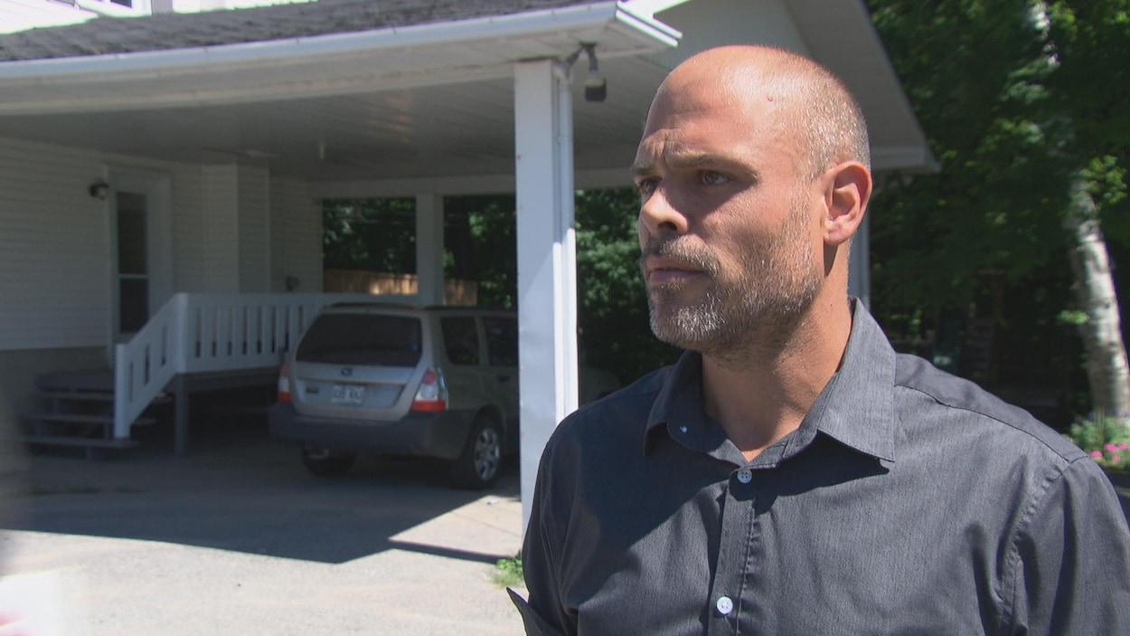 Samuel Roy répond aux questions d'un journaliste devant une résidence.