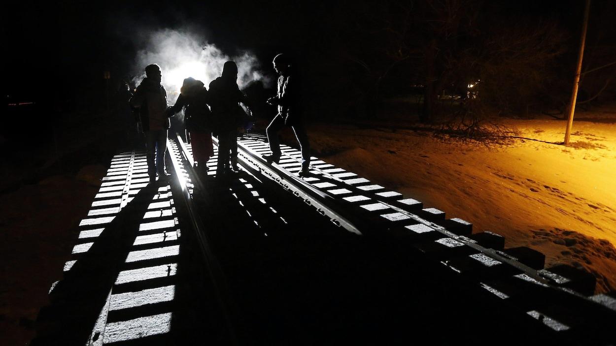 Des demandeurs d'asile marchent sur voie ferrée, dans la noirceur.