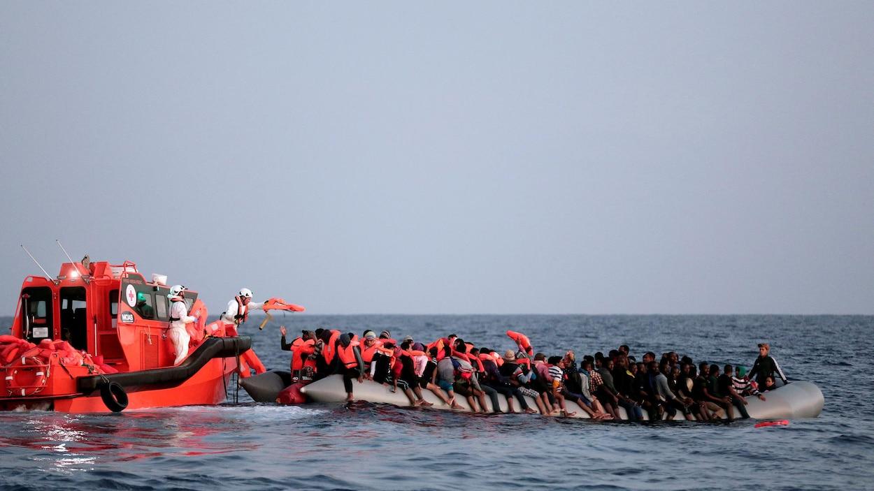 Des dizaines de migrants sur une embarcation gonflable rescapés en mer par la Croix-Rouge.