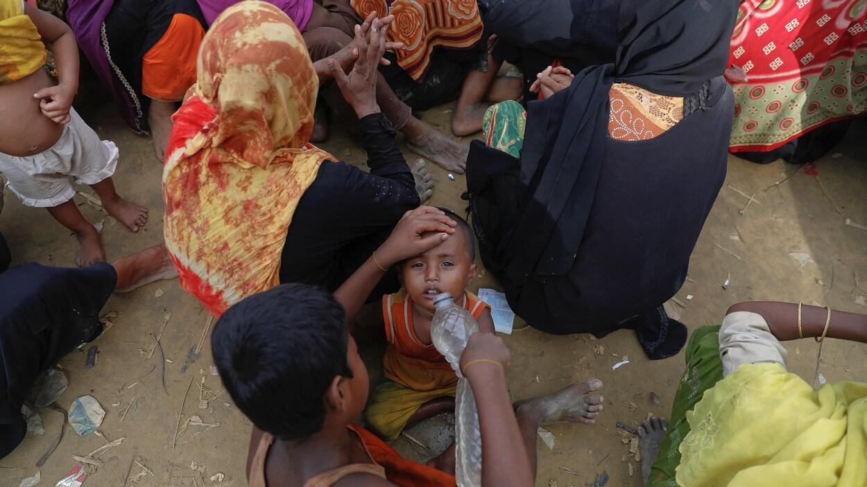 Un garçon donne à boire à son jeune frère dans l'attente d'une distribution d'aide humanitaire dans un camp du Bangladesh.