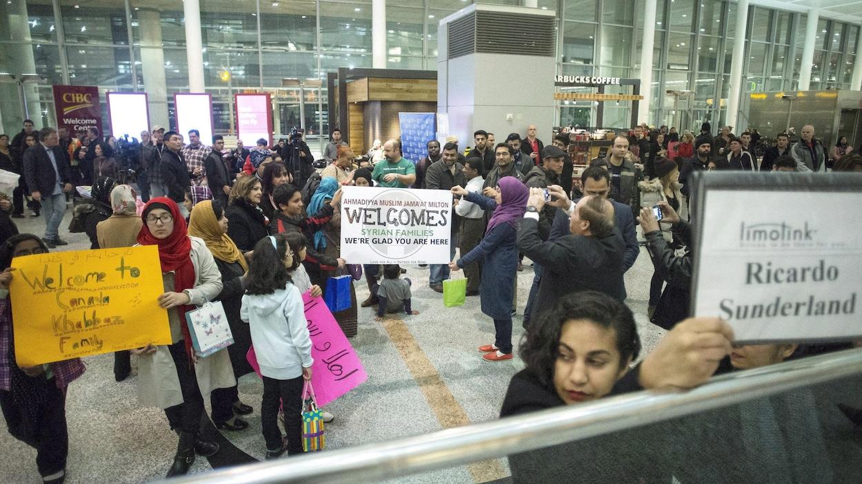 Des groupes de parrainage attendent des familles syriennes à l'aéroport de Toronto en décembre 2015.