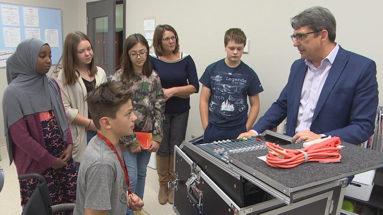 Autour d'une grande boîte noire comportant un clavier de boutons sur le dessus, sont rassemblés cinq jeunes élèves et deux adultes.