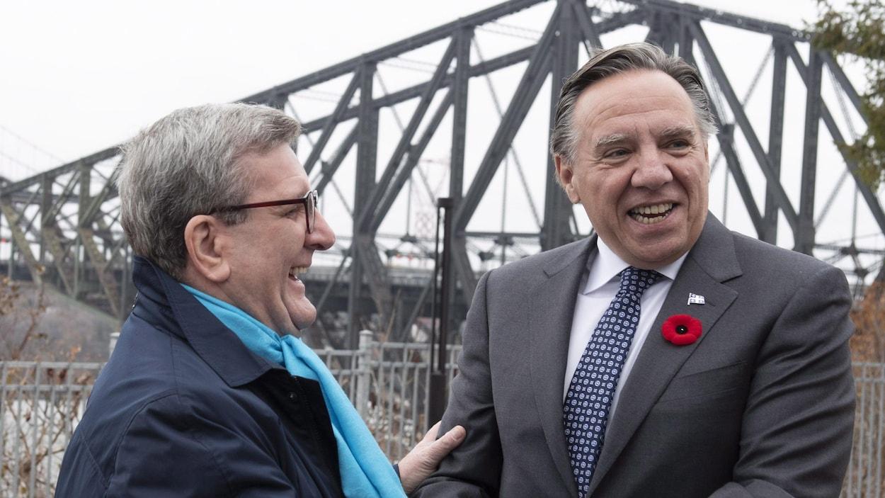 Régis Labeaume et François Legault rient ensemble après leur rencontre. On aperçoit, à l'arrière-plan, le pont de Québec.
