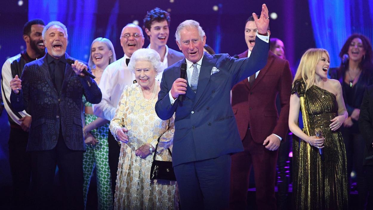 La reine Élisabeth II, sur scène, entourée de son fils Charles et de plusieurs artistes, dont Tom Jones, Shawn Mendes et Kylie Minogue.