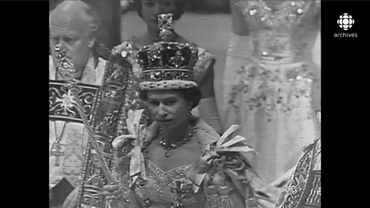 La reine Élisabeth II, sceptre à la main avec sa lourde couronne sur la tête, en procession à la suite de son couronnement.