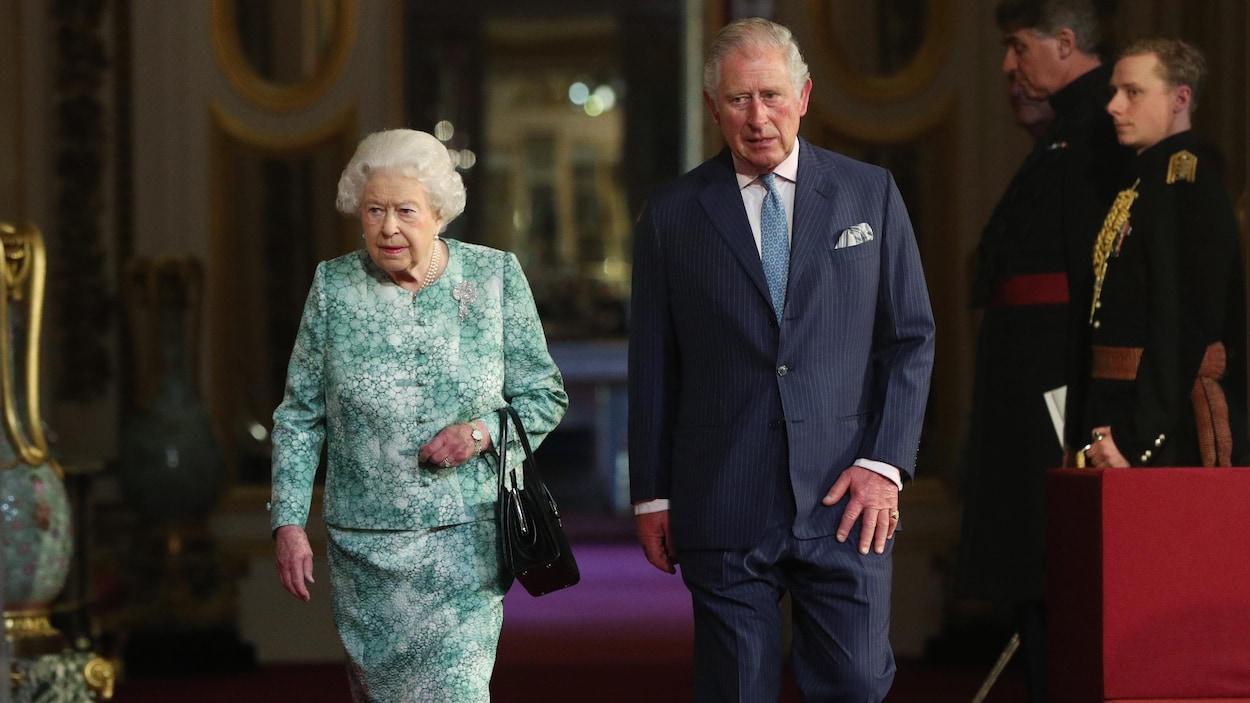 Élisabeth II et le prince de Galles marchent côte à côte sur le tapis rouge du palais de Buckingham.