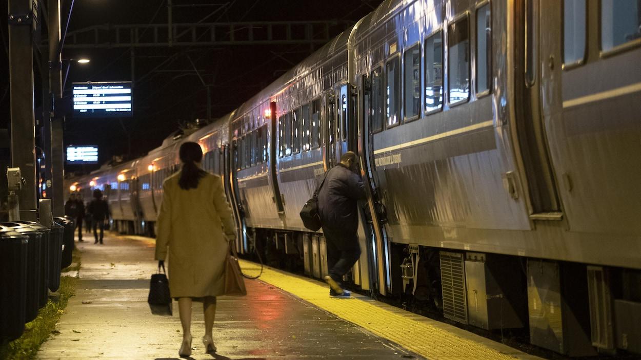 Une femme marche sur le quai alors qu'un train s'apprête à quitter la gare à Deux-Montagnes.