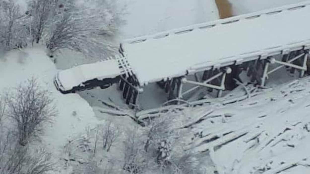 Un camion se trouve sur un pont affaissé. Plusieurs centimètres de neige sont accumulés sur le véhicule et sur le pont.