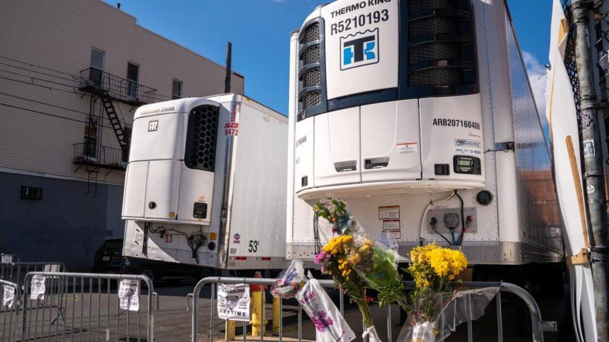 Des fleurs sont accrochées à la barrière près de deux camions frigorifiques.