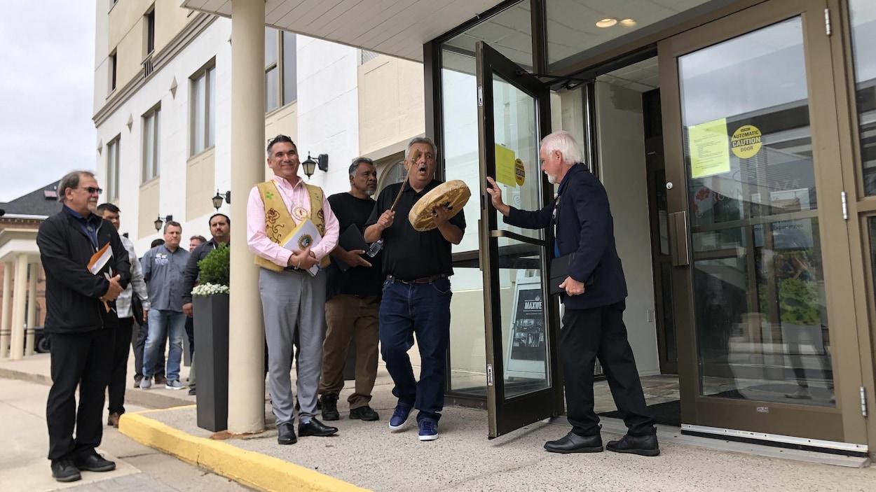 Un groupe de représentants des Premières Nations sur le perron d'un édifice. L'un d'entre eux frappe sur un tambour. Un homme leur ouvre la porte.