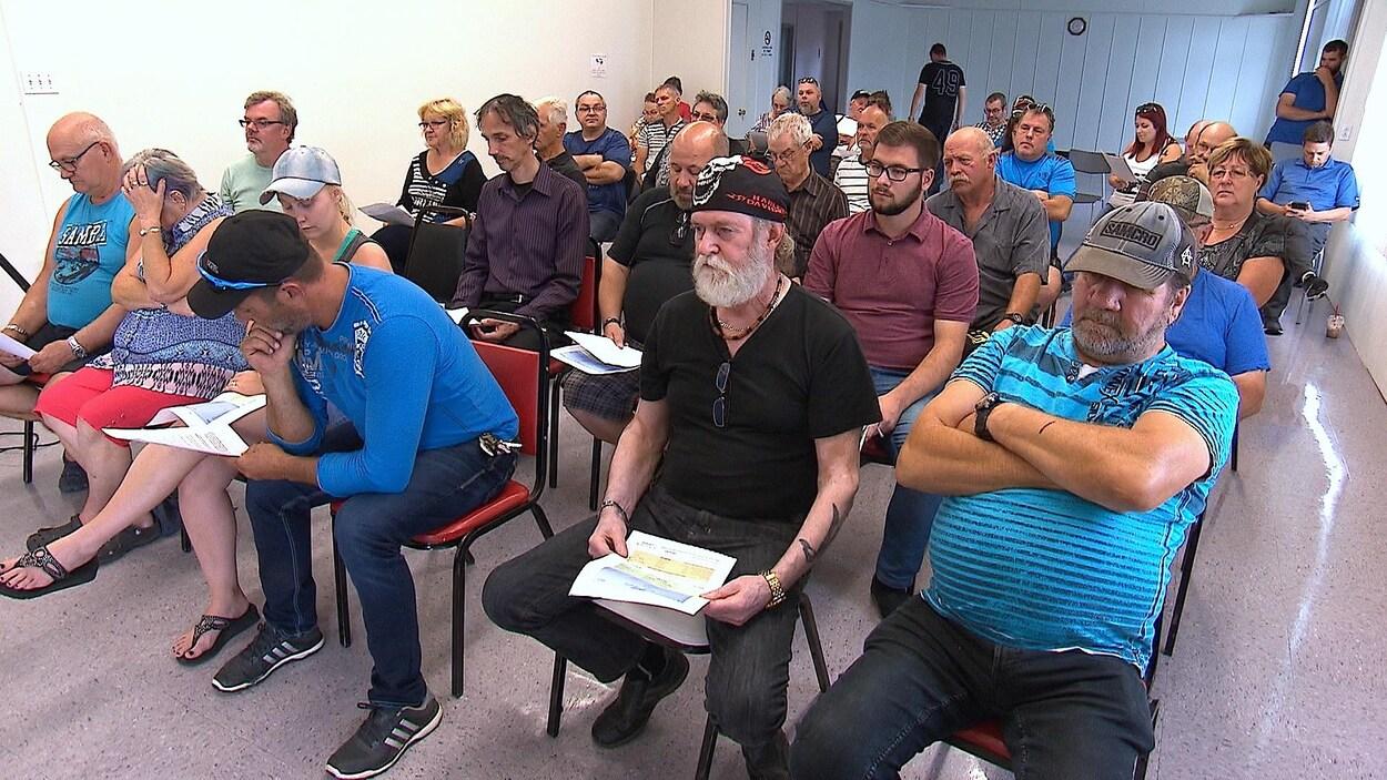 Des citoyens sont assis en rangées dans une assemblée citoyenne à Pointe-Lebel